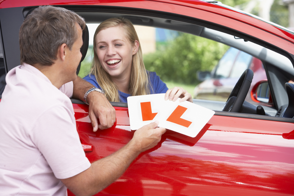 Photo of girl with L plates on driving lesson